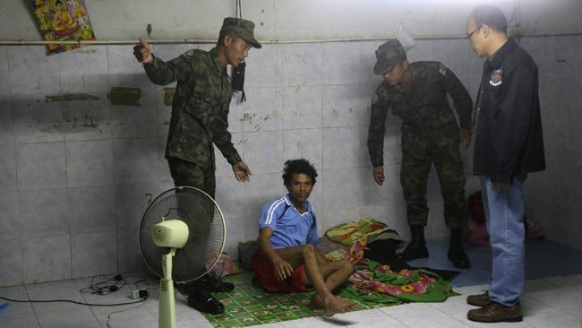 Thai soldiers and an investigator wake a worker during a November 2015 raid on a shrimp shed in Thailand. Credit: Dita Alangkara / AP.